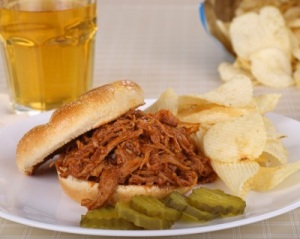 BBQ pulled pork sandwich with pickles and potato chips